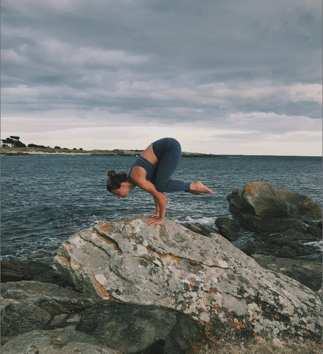 Marie pratiquant le yoga sur rocher face à la mer - Yogissime